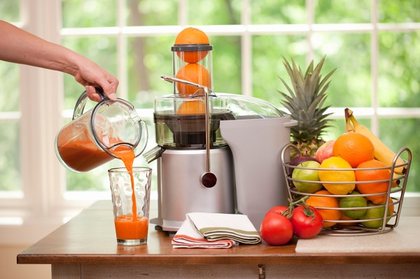 Pouring a glass of fresh blended organic juice.